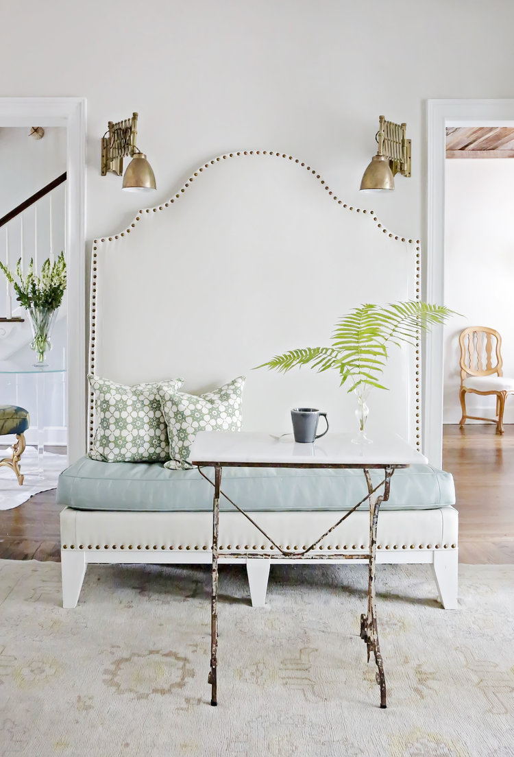 A chic breakfast nook with curved banquette with nailhead trim, brass adjustable wall sconces, and vintage metal table. Aqua upholstery is gorgeous! Rachel Halvorson Inspired Decorating Tips. #breakfastnook #banquette #aqua #cottagestyle #vintagestyle