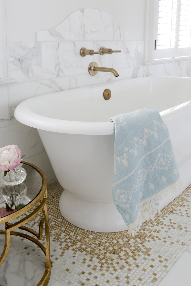 Luxurious white marble bathroom with marble mosaic white tile mixed with gold tiles, freestanding tub, and wall mounted brass fixtures. Rachel Halvorson Inspired Decorating Tips. #whitebathroom #marble #mosaic #whiteandgold #brass