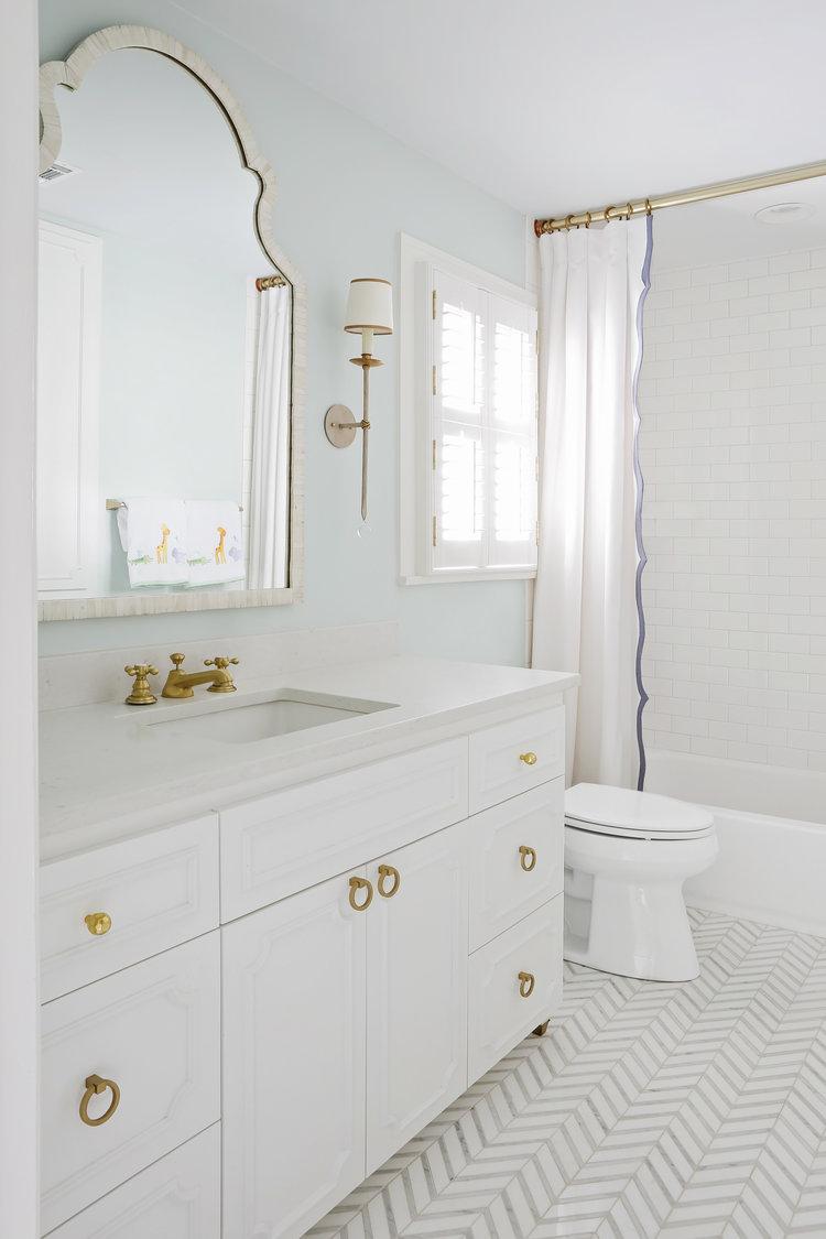 White bathroom with pale aqua wall, brass hardware, and dramatic herringbone tile floor. Rachel Halvorson Inspired Decorating Tips. #whitebathroom #herringbonetile #lightblue