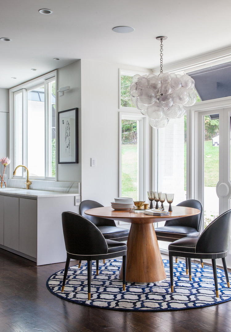 Kitchen dining area with round modern sleek wood table and black leather chairs. Rachel Halvorson Inspired Decorating Tips