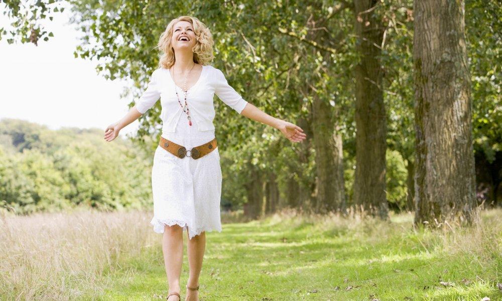 Woman walking on path smiling