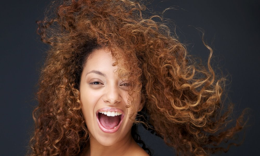 Portrait of a fun and happy young woman laughing with hair blowing