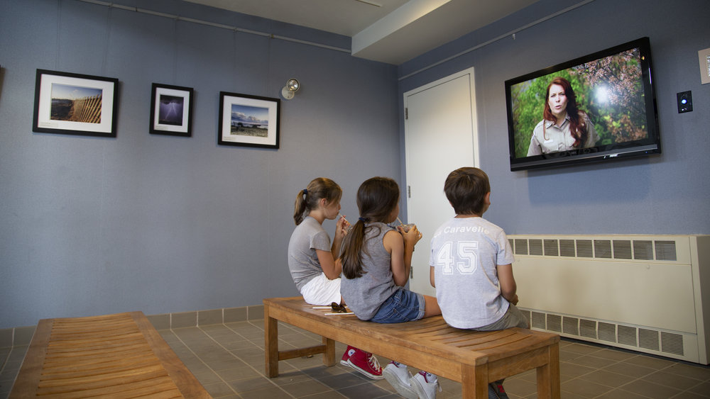 Visitors enjoy the film 'Spectacle Island', on display in the Spectacle Island National Park Area visitor center.