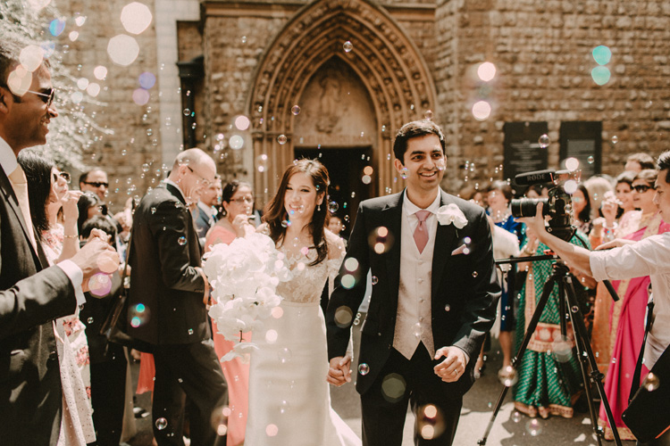 asian bride and groom recessional with bubbles in london city wedding