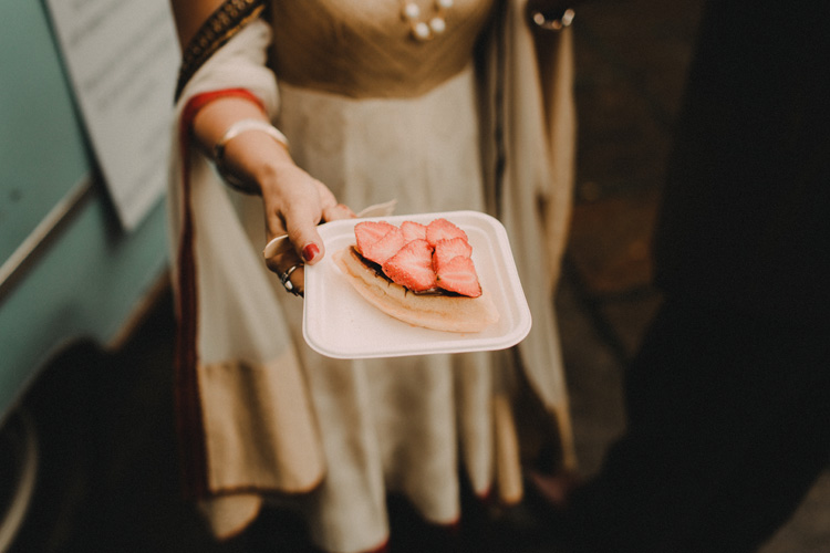 hindu bride shows dessert at hindu wedding reception
