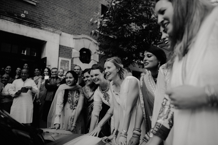 bridesmaids stop indian bride and groom from leaving hindu wedding ceremony
