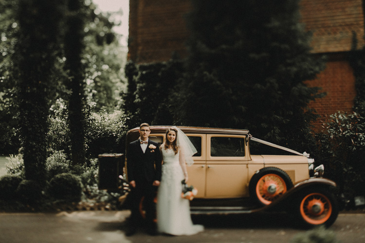 bride and groom stand next to vintage car in surrey wedding