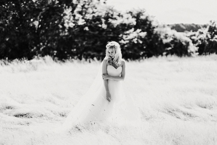 boho bride stands in hay field in chesham wedding