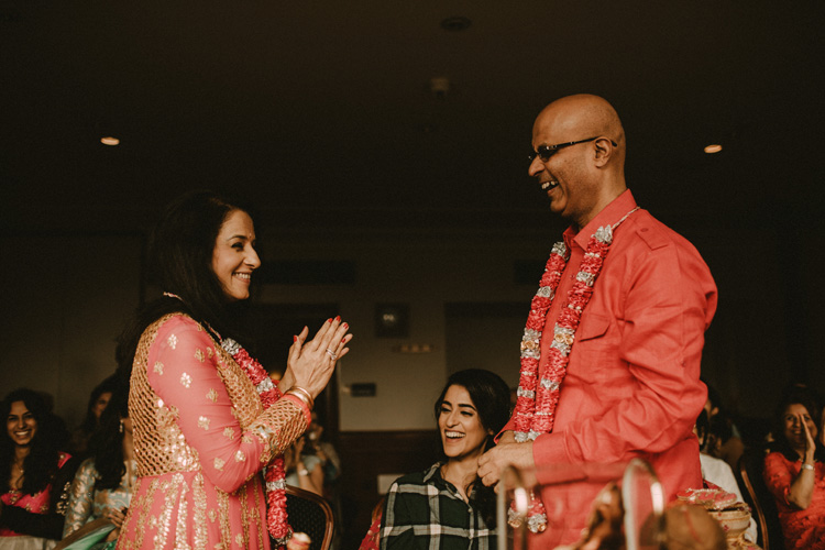 brides mum and dad laugh after finishing ritual in puja