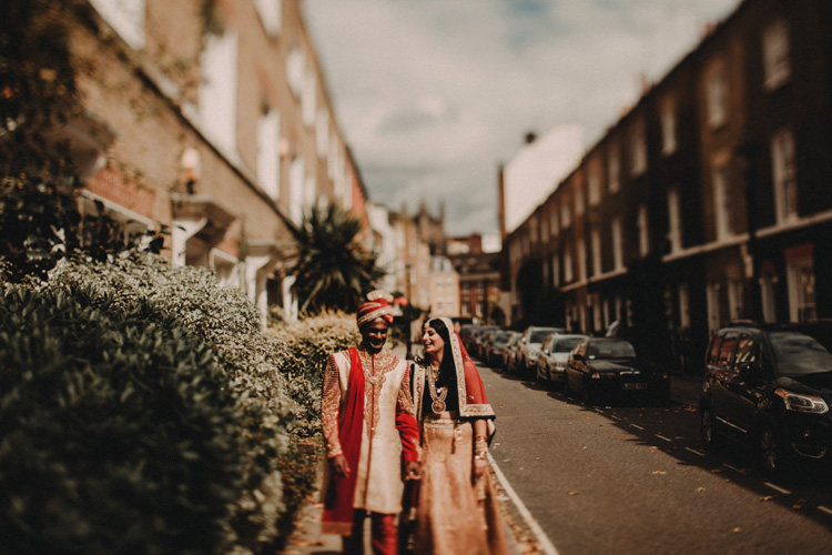 indian bride and groom hold hands walking down london street