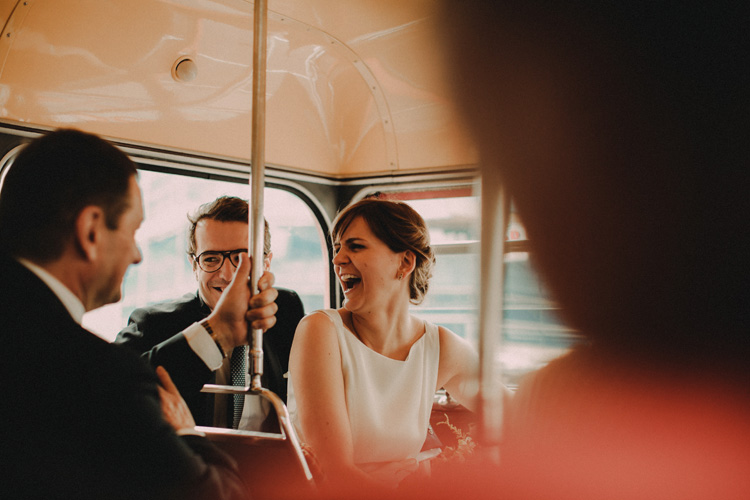 russian bride laughs with guests on red london bus