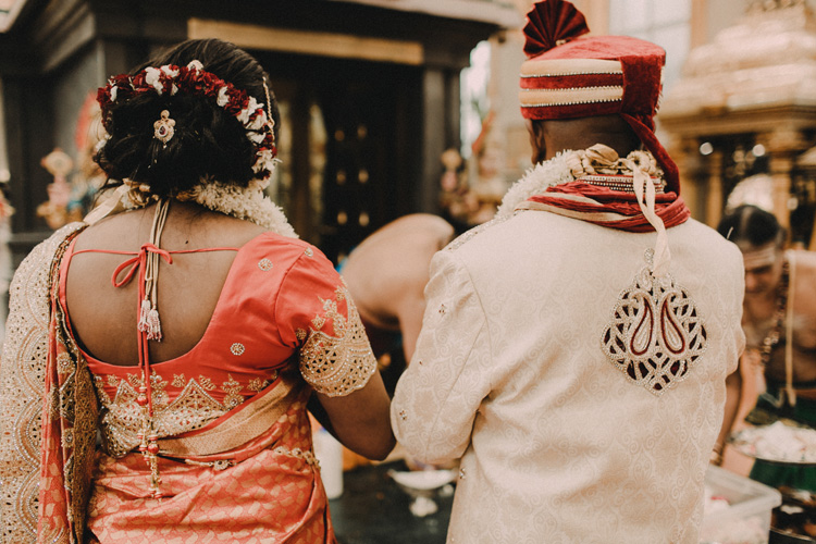 bride and groom pray in hindu temple after traditional hindu wedding