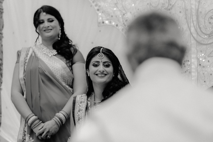 indian bride looks on smiling to father during hindu ceremony