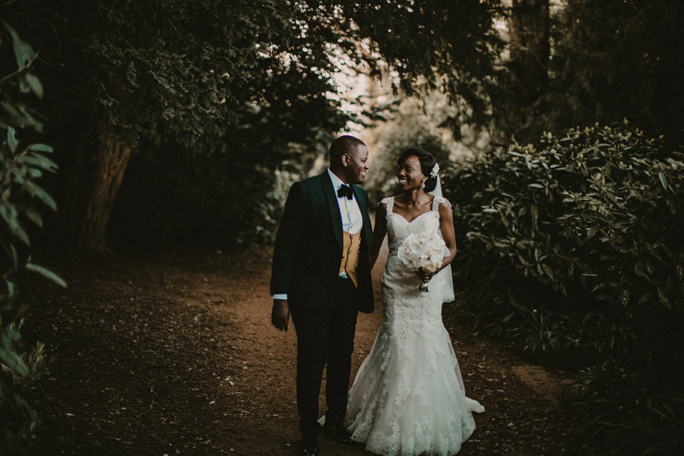 african bride and groom hold hands and share laugh at hylands house wedding