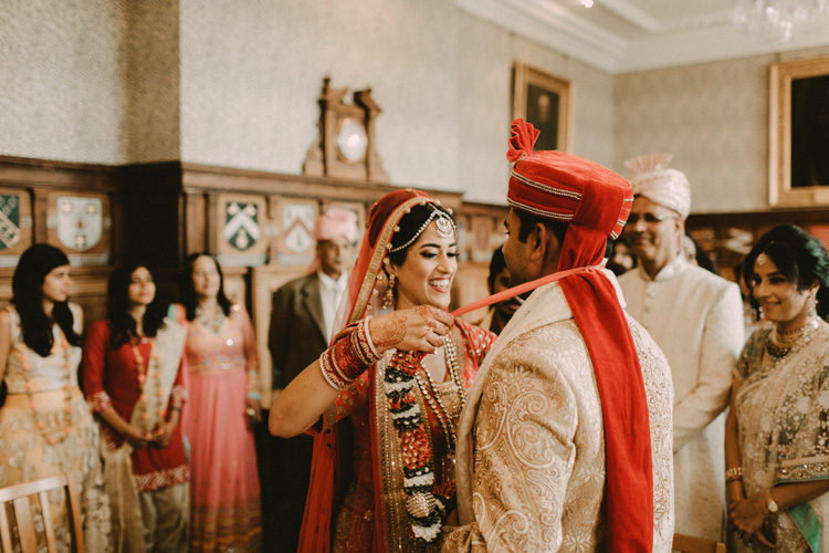 hindu bride ties garland around grooms neck in hindu ceremony at the great hall