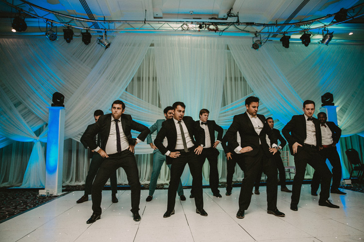 groom and groomsmen dance for bride during hindu wedding reception