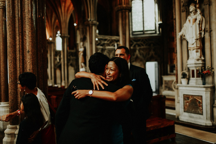 groom hugs family member after farm street church wedding
