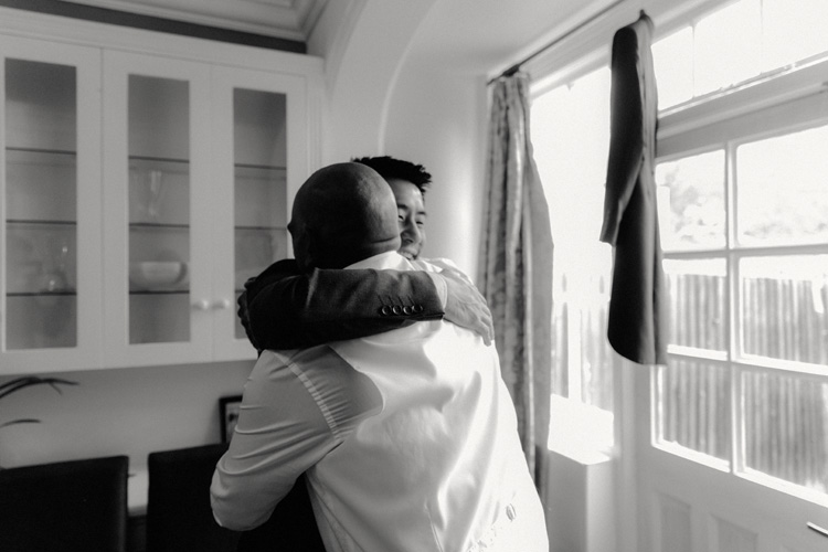 groom and best man embrace whilst getting ready for syon park wedding