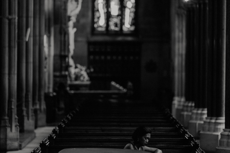 wedding guest sits in pew in farm street church wedding