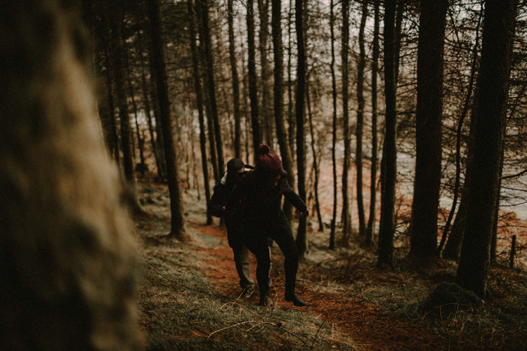 couple hold hands walking in forest in glencoe engagement