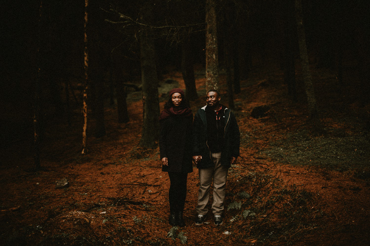 couple hold hands in forest during glencoe engagement
