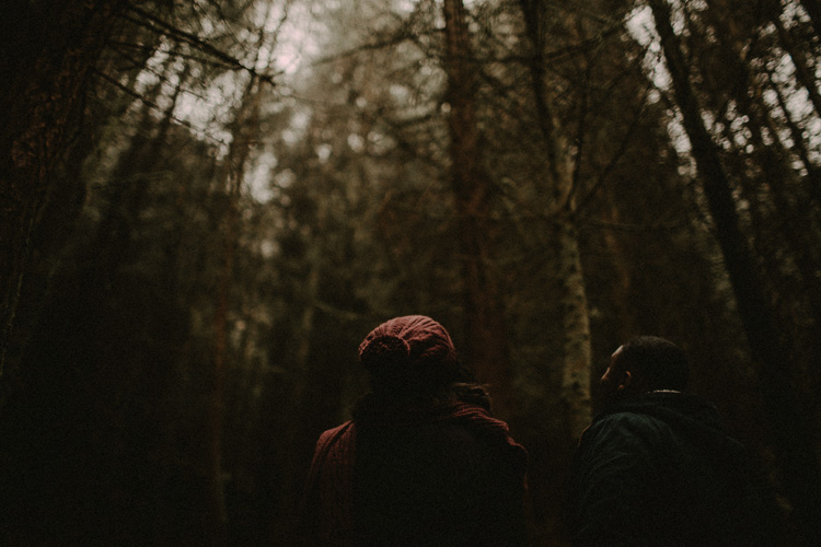 couple look up in forest during glencoe engagement
