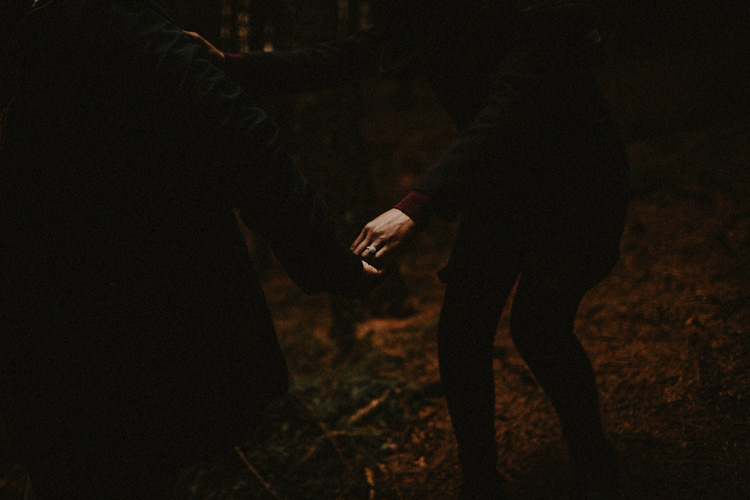 close up of couple holding hands in forest during glencoe engagement