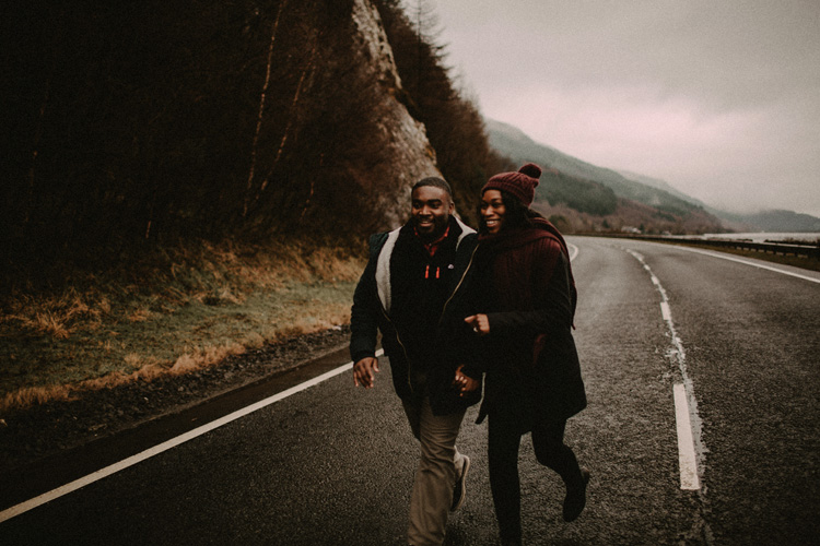 couple hold hands whilst running in road during glencoe engagement