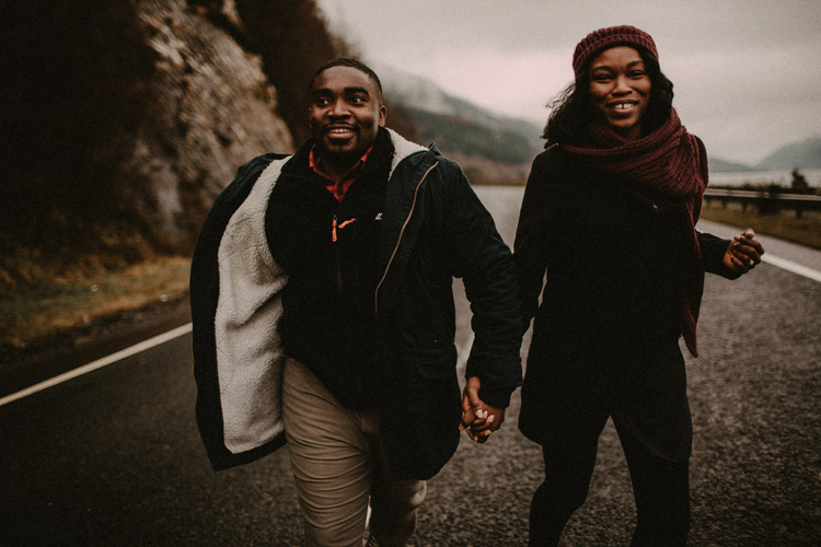 couple hold hands laughing whilst running in road during glencoe engagement