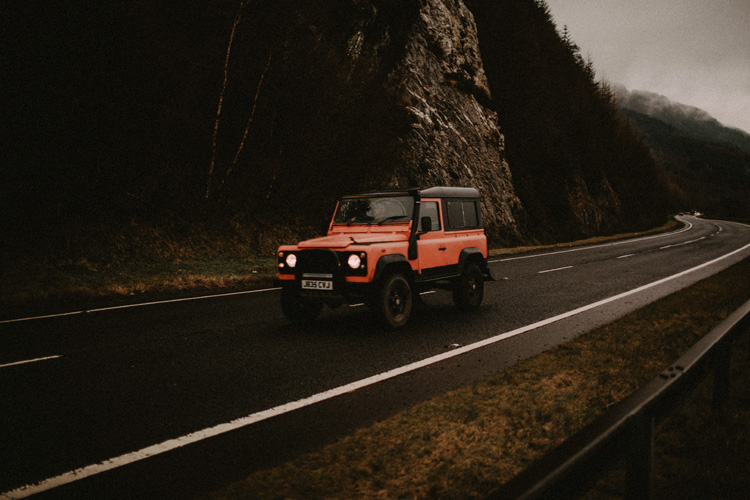 red land rover drives by during glencoe engagement
