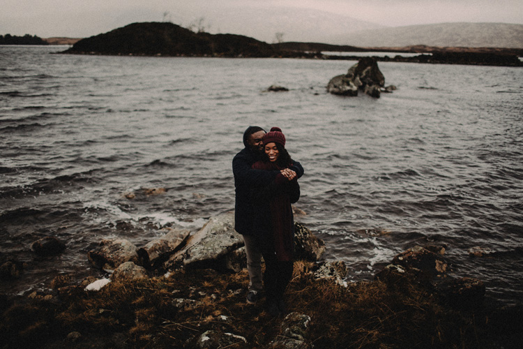 couple share laughs by river during glencoe engagement
