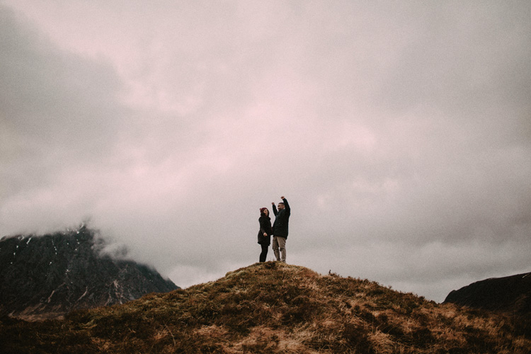 couple celebrate completing hike of glencoe during glencoe engagement
