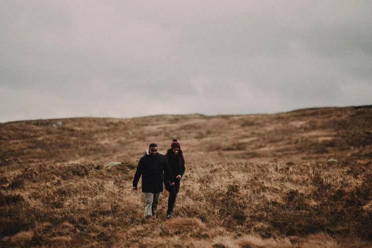 couple hold hands hiking through glencoe during glencoe engagement session