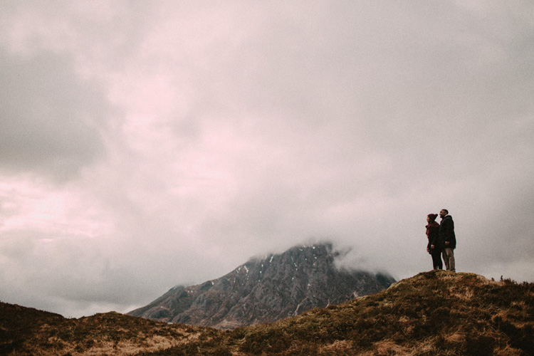 couple stand and look at glencoe mountain during glencoe engagement