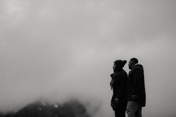 couple hold hands looking up at glencoe mountain during glencoe engagement