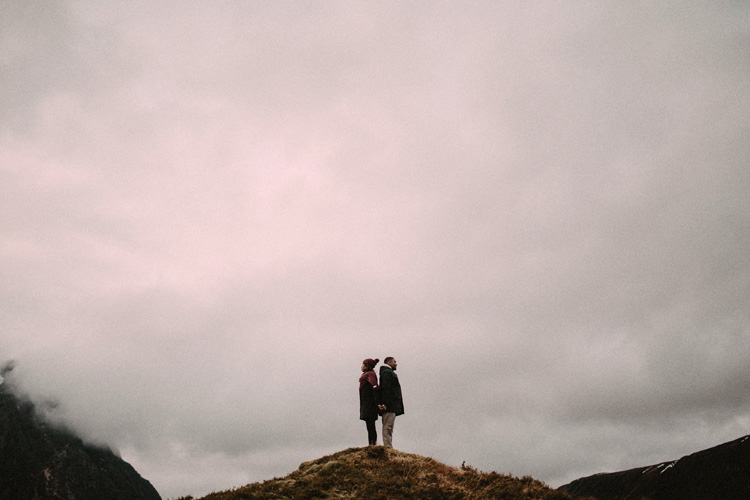couple hold hands facing back to back during glencoe engagment