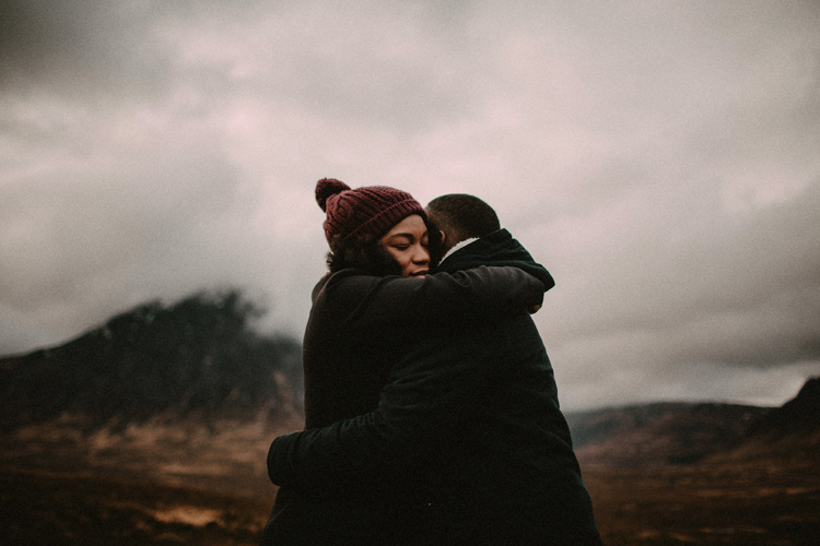 couple share intimate moment hugging on glencoe mountain