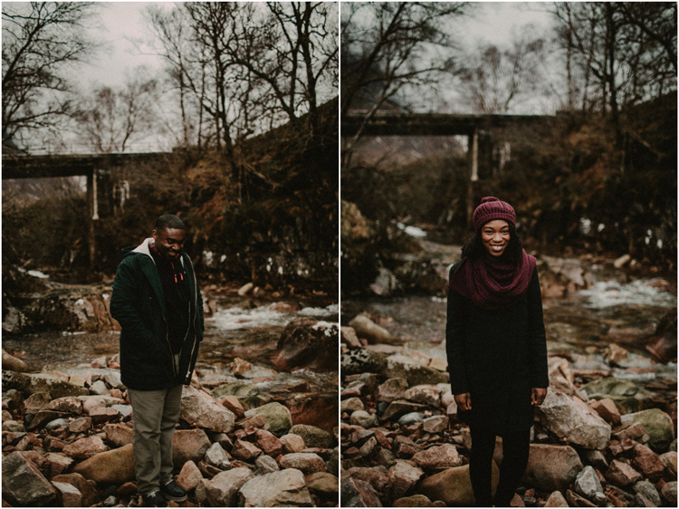 couple stand by river in glencoe mountain during glencoe engagement