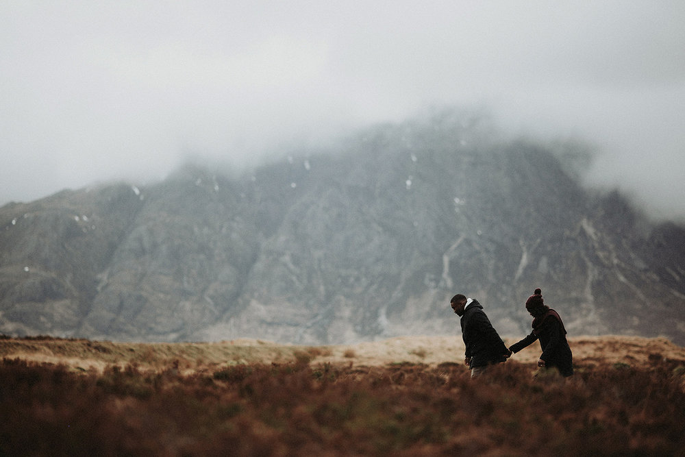 couple share intimate moment walking through glencoe mountain