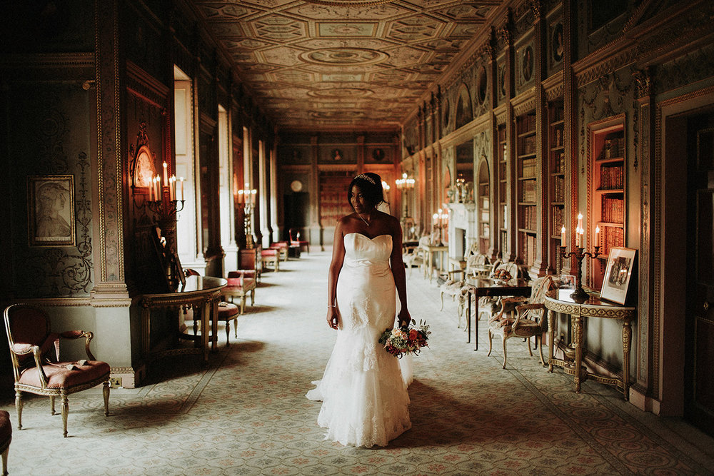 Copy of bride looks out window in syon park wedding