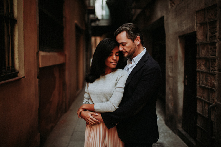 couple hold each other intimately in the streets of the gothic quarter in Barcelona
