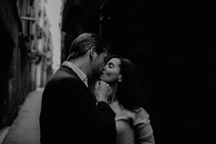couple share an intimate kiss in the streets of the gothic quarter in Barcelona