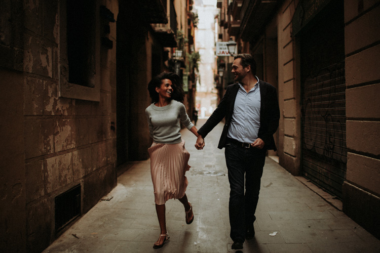couple hold hands running through the streets of barcelona