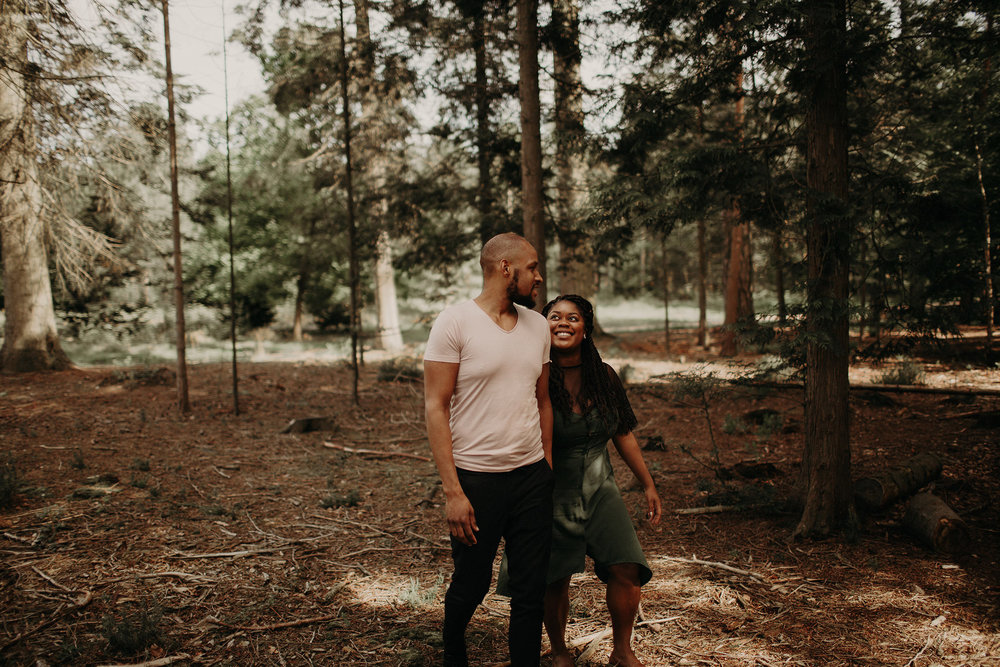 engaged couple holding hands walking in the forest
