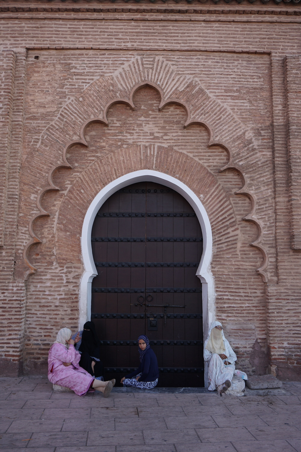 Women in Morocco gather at the door of the largest Mosque in Marrakesh.