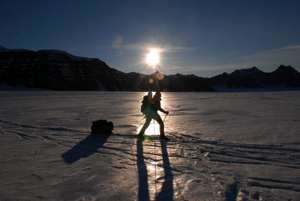 Silhouette of Ben returning to base camp in front of the midnight sun.