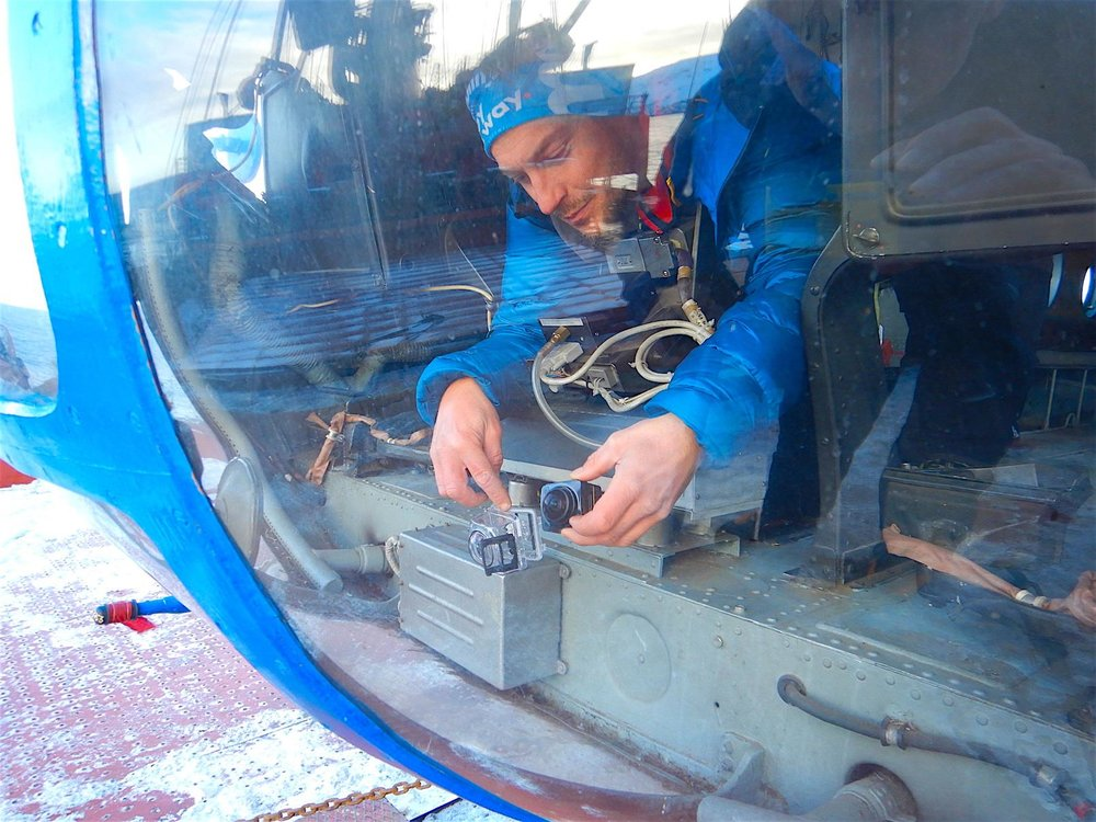 Setting up a Kodak fish-eye cam in the helicopter cockpit. The video imaging will be used to 3Dmodel the islands we will study