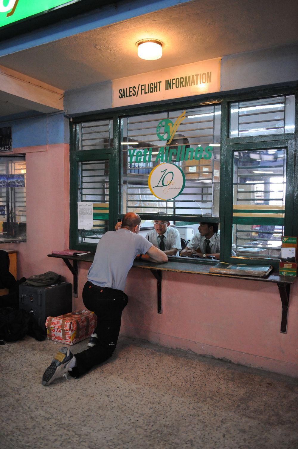 Yves 'prays' for early departure at Yeti Airlines' office.