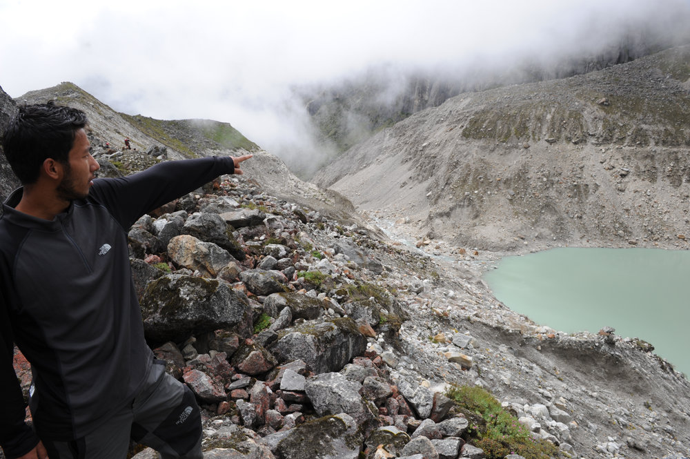 Samir shows the top of the 100m-high and 300m-wide moraine dam which collapsed in 1998.
