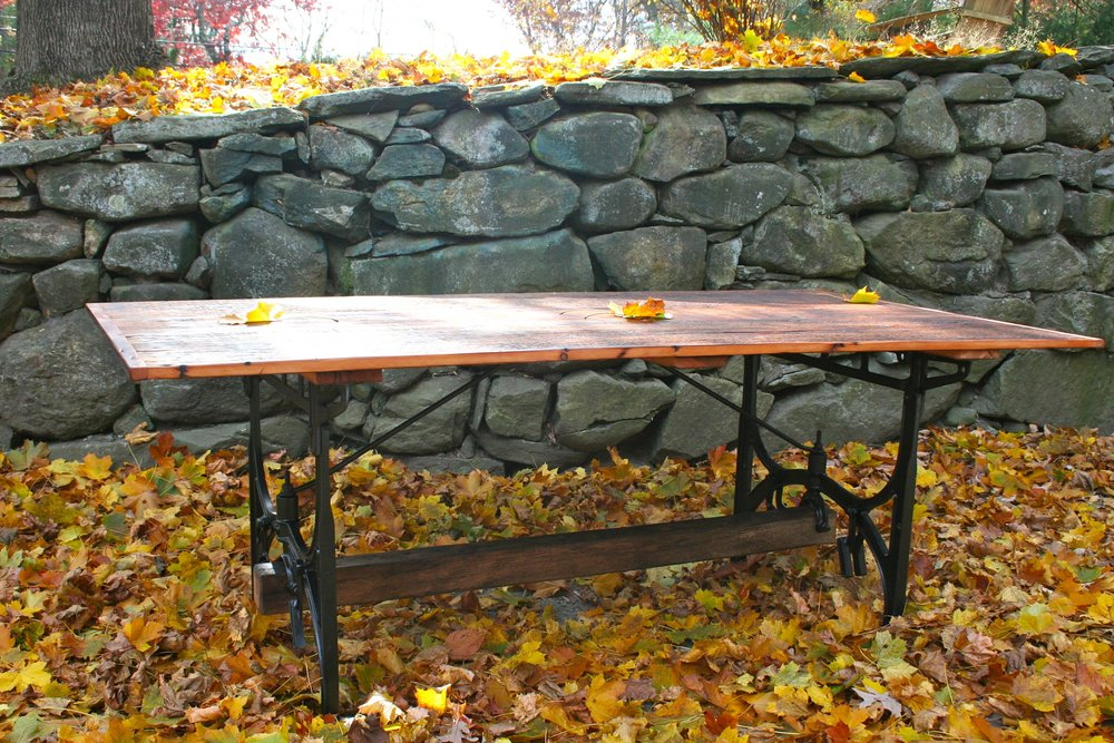 Cast iron legs from an industrial sewing machine support a table made from reclaimed 1800's cider house wood.